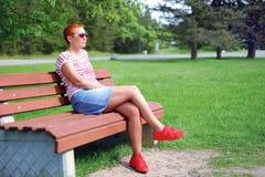 Atrakcyjna młoda kobieta w czarnych szkłach, siedzi w lato parku na ławce obrazy stock