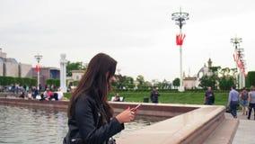 Atrakcyjna młoda kobieta w jaskrawym świetle słonecznym, wyszukuje ogólnospołecznych środki na telefonie komórkowym zbiory wideo