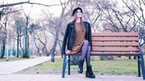 Atrakcyjna młoda kobieta w mody sukni, czarnym kapeluszu, kostka butach i skórzanej kurtce, siedzi samotnie na ławce w parku wewn zbiory
