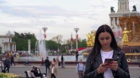 Atrakcyjna młoda kobieta w parku, pisać na maszynie na telefonie komórkowym, ono uśmiecha się swobodny ruch zbiory