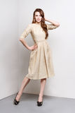 Atrakcyjna młoda kobieta w złotej sukni stoi w mody pozie Zdjęcia Stock
