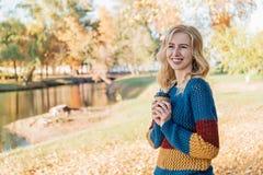 Atrakcyjna młoda kobieta z kędzierzawym włosy pije kawę outside obrazy royalty free