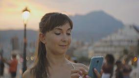 Atrakcyjna młoda kobieta z smartphone Uśmiechnięty caucasian kobiety gawędzenie na telefonie komórkowym na lato zmierzchu miejsco zbiory wideo