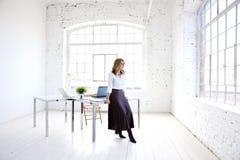 Atrakcyjna młoda kreatywnie kobiety pozycja przy biurowym biurkiem i przyglądającym zamyśleniem zdjęcia stock