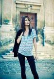 Atrakcyjna młoda brunetka pozuje na ulicie. Zdjęcia Stock