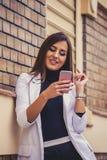 Atrakcyjna młoda kobieta texting na jej telefonie komórkowym Obrazy Royalty Free