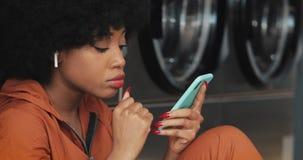 Atrakcyjna m?oda kobieta u?ywa smartphone przy laundromat Jest by? ubranym bezprzewodowe s?uchawki i ?piew indoors obrazy stock