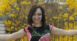 Atrakcyjna m?oda kobieta w sukni z kwiatami robi ?miesznym twarzom fotografia stock