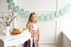 Atrakcyjna mała dziewczynka w kolorowej sukni pozuje i ono uśmiecha się obraz stock