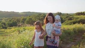 Atrakcyjna matka i jej syn w jej rękach przy zmierzchem córki i małego zbiory wideo