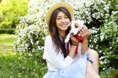 Atrakcyjna modniś młoda kobieta pójść dla spaceru w parku, bawić się z ślicznym dźwigarki Russell teriera szczeniakiem na jasnym  Zdjęcia Stock