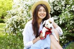Atrakcyjna modniś młoda kobieta pójść dla spaceru w parku, bawić się z ślicznym dźwigarki Russell teriera szczeniakiem na jasnym  Zdjęcie Stock