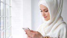 Atrakcyjna muzu?ma?ska kobieta w hijab pisa? na maszynie wiadomo?? na smartphone zdjęcie royalty free