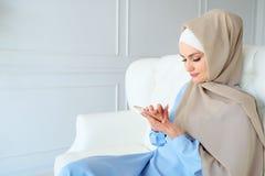 Atrakcyjna muzu?ma?ska kobieta w hijab wyszukuje internet strony w smartphone obsiadaniu na kanapie obraz royalty free