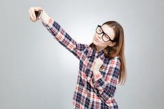 Atrakcyjna nastoletnia dziewczyna w szkłach używać smartphone i brać selfie obrazy royalty free