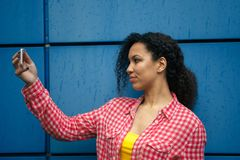 Atrakcyjna oliwkowa kobieta ogląda wideo na jej telefonie komórkowym podczas gdy siedzący w sklep z kawą Modniś dziewczyna opowia zdjęcia stock