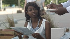 Atrakcyjna oszałamiająco młoda afro amerykańska dama siedzi samotnie przy kawiarnia stołem, przygotowywającym robić rozkazowi Zdjęcie Royalty Free