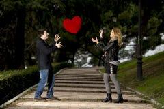 Atrakcyjna para bawić się z miłości serca poduszką Obrazy Stock