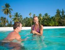 Atrakcyjna para ma fan na tropikalnej plaży zdjęcia royalty free