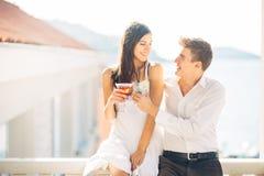 Atrakcyjna para pije koktajle, cieszy się wakacje Ono uśmiecha się, przyciągam each inny Flirtować i uwiedzenie obraz stock