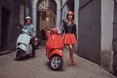Atrakcyjna para, przystojny mężczyzna i seksowna żeńska pozycja na starej ulicie z dwa retro hulajnoga, zdjęcie royalty free
