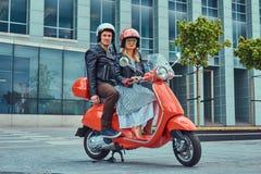 Atrakcyjna para, przystojny mężczyzna wpólnie i seksowna żeńska jazda na czerwonej retro hulajnoga w mieście, obraz royalty free