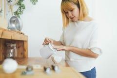 Atrakcyjna piękna azjatykcia kobieta cieszy się ciepłą kawę w kuchni przy ona do domu Obraz Royalty Free