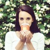 Atrakcyjna, piękna dziewczyna: cieszyć się filiżankę kawy w parku zdjęcie stock