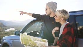 Atrakcyjna potomstwo para używa mapę dla wybierać kierunek dla podwyżki na halnym tle zdjęcie wideo