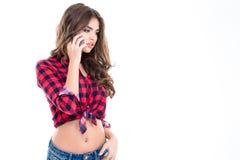 Atrakcyjna powabna kobieta opowiada na telefonie komórkowym w w kratkę koszula obrazy royalty free