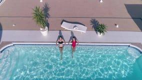 Atrakcyjna przyjaciel dziewczyna w Swimsuit relaksuje w błękitnym falowaniu na lato odpoczynku i basenie cześć zbiory wideo