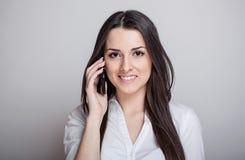 Atrakcyjna przypadkowa młoda kobieta opowiada na jej telefon komórkowy Fotografia Stock