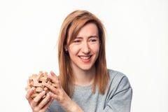 Atrakcyjna 24 roczniak biznesowej kobiety patrzeje wprawiać w zakłopotanie z drewnianą łamigłówką Obraz Royalty Free