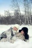 Atrakcyjna rodziny matka, córka i kłaść na śniegu w zima parku Obraz Royalty Free