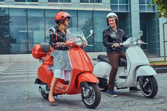 Atrakcyjna romantyczna para, przystojny mężczyzna i seksowna kobieta stoi z dwa retro Włoskimi hulajnoga przeciw a, obraz royalty free
