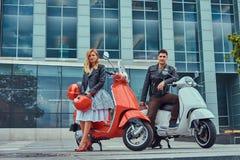 Atrakcyjna romantyczna para, przystojny mężczyzna i seksowna kobieta stoi z dwa retro Włoskimi hulajnoga przeciw a, zdjęcie royalty free
