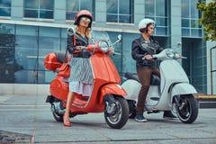 Atrakcyjna romantyczna para, przystojny mężczyzna i seksowna kobieta stoi z dwa retro Włoskimi hulajnoga przeciw a, obrazy royalty free