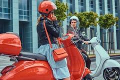 Atrakcyjna romantyczna para, przystojny mężczyzna i seksowny żeński obsiadanie na retro Włoskich hulajnoga przeciw drapaczowi chm obraz royalty free