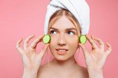Atrakcyjna rozochocona kobieta z ręcznikiem zawijającym wokoło jej głowy, trzyma ogórkowych plasterki blisko jej twarzy na różowy zdjęcie royalty free