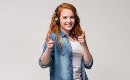 Atrakcyjna rudzielec dziewczyna wskazuje ona przy kamerą w hełmofonach palce obrazy royalty free