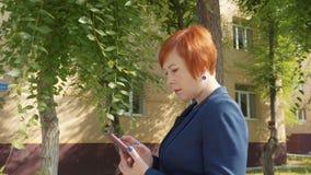 Atrakcyjna rudzielec kobieta wyszukuje telefon i patrzeje daleko od zbiory wideo