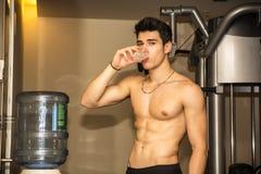Atrakcyjna sportowa młody człowiek woda pitna wewnątrz Fotografia Stock