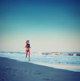 Atrakcyjna sporty dziewczyna z wysokim prędkość bieg wzdłuż plaży przy zadziwiającym zmierzchem z morzem na tle Zdjęcie Royalty Free