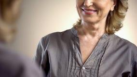 Atrakcyjna starsza kobieta patrzeje odbicie w lustrze z doskonalić uśmiechem fotografia royalty free