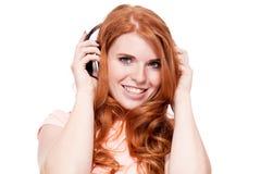 Atrakcyjna szczęśliwa kobieta z hełmofonami słucha muzyka odizolowywająca obrazy royalty free