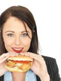 Atrakcyjna Szczęśliwa Młoda Biznesowa kobieta Je kurczaka hamburger Obraz Stock