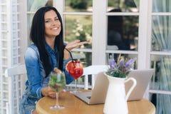 Atrakcyjna szczęśliwa młoda brunetki kobieta ubierał w drelichowej koszula, siedzący w cukierniany outside, ono uśmiecha się some obraz stock