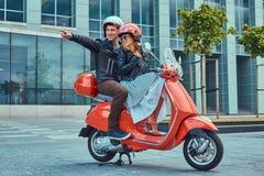 Atrakcyjna szczęśliwa para, przystojny mężczyzna i seksowna żeńska jazda na czerwonej retro hulajnoga w mieście, wpólnie zdjęcie royalty free