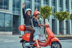 Atrakcyjna szczęśliwa para, przystojny mężczyzna i seksowna żeńska jazda na czerwonej retro hulajnoga w mieście, wpólnie fotografia royalty free