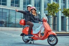 Atrakcyjna szczęśliwa para, przystojny mężczyzna i seksowna żeńska jazda na czerwonej retro hulajnoga w mieście, wpólnie obrazy stock